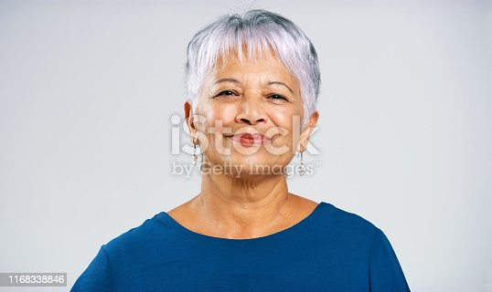 Portrait of a cheerful elderly woman standing against a grey background inside of a studio