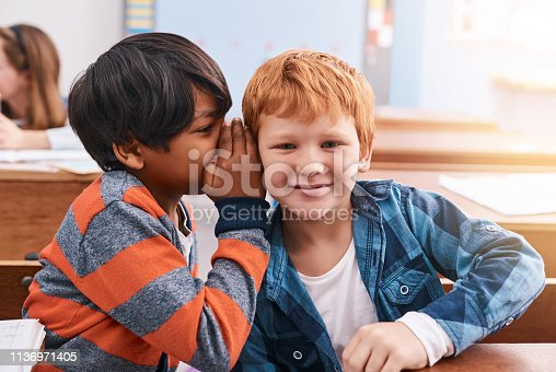 Cropped shot of elementary school kid whispering into another student's ear inside of the classroom