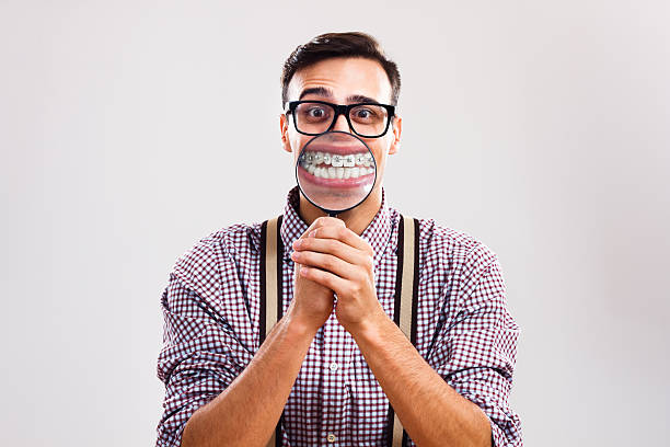 I have braces and I am still handsome! Nerdy man is holding loupe and showing his teeth with braces. suspenders stock pictures, royalty-free photos & images