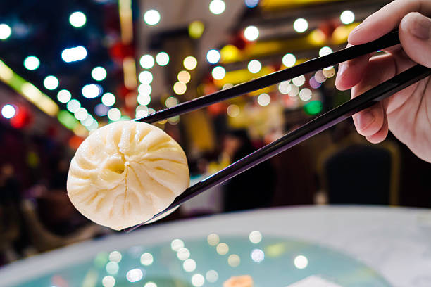 Have chinese steamed buns with chopsticks stock photo