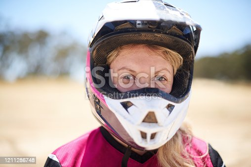 Shot of a young woman going dirt biking on an outdoor track
