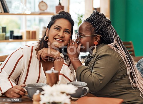Shot of two young women gossiping at a cafe