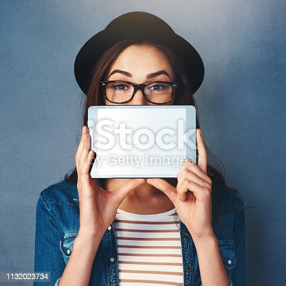 Shot of an attractive young woman holding tablet in front of her face in studio