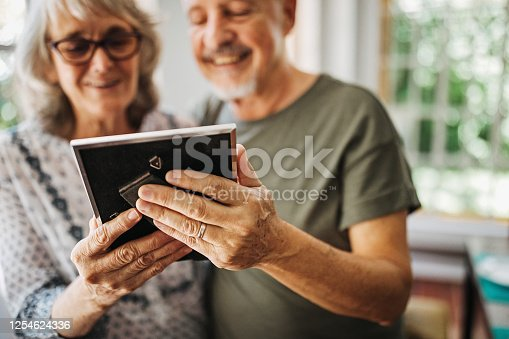 Senior woman in nursing home, looking at picture frame