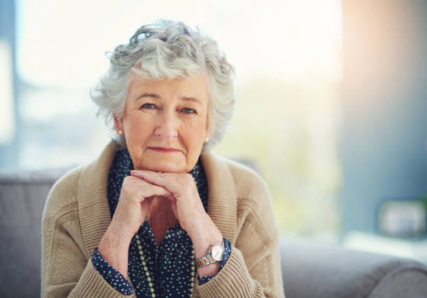 I have much to tell you about life Portrait of a senior woman sitting on the sofa at home one mature woman only stock pictures, royalty-free photos & images