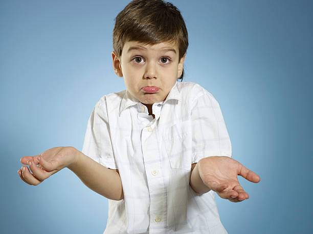 I Have No Idea Little boy shrugs shoulders. shrugging stock pictures, royalty-free photos & images