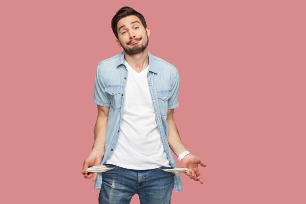 I have no money more. Portrait of sad bankrupt bearded young man in blue casual style shirt standing and showing his empty pocket and looking at camera. I have no money more. Portrait of sad bankrupt bearded young man in blue casual style shirt standing and showing his empty pocket and looking at camera. indoor studio shot, isolated on pink background empty wallet stock pictures, royalty-free photos & images