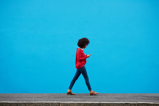 Shot of a fashionable young woman using her cellphone while walking through the city