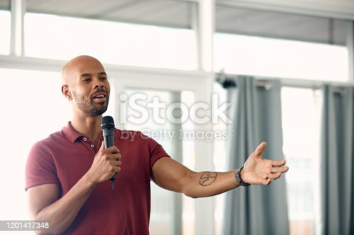 Cropped shot of a handsome young man speaking over a microphone