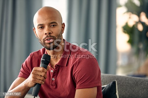 Cropped shot of a young man sitting on a sofa while speaking over a microphone