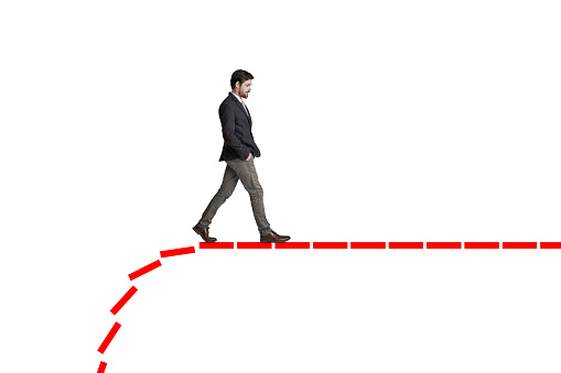 Shot of a businessman walking along a line that's falling behind him against a white background