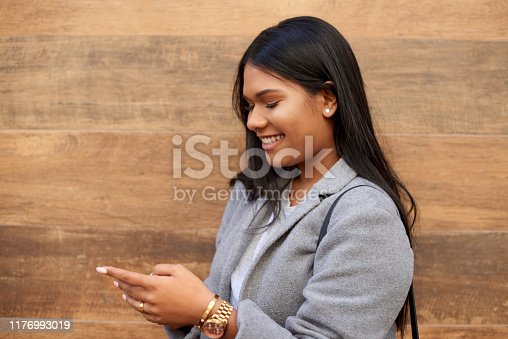 Cropped shot of an attractive young woman smiling while using a smartphone outdoors