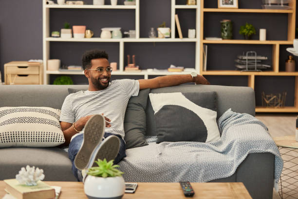 I have the place all to myself Shot of a handsome young man relaxing on the sofa at home bachelor stock pictures, royalty-free photos & images