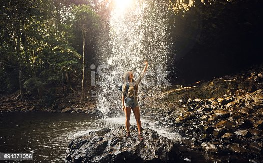 Shot of a young woman taking a selfie by a waterfall in nature