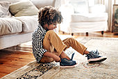 Shot of a determined young little boy trying to put on his shoes inside at home during the day