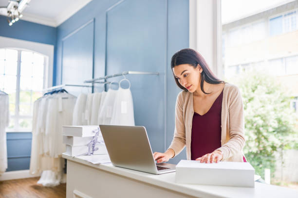 I have to notify this customer that her dress is ready Shot of a shop assistant using a laptop in a bridal shop sell online stock pictures, royalty-free photos & images