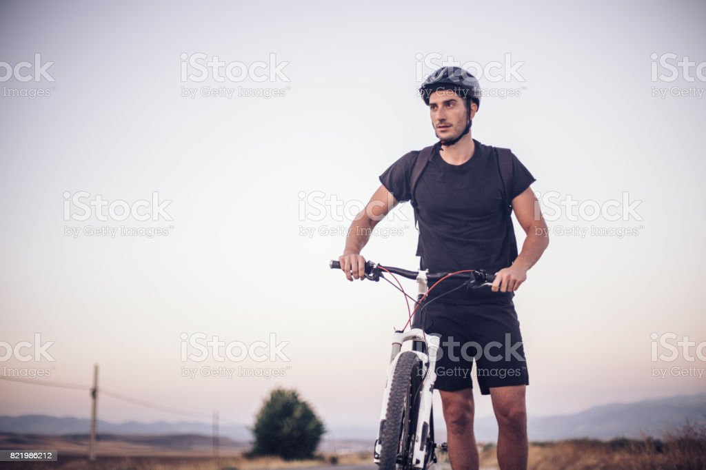 Man standing near mountain bike on a country road