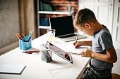 Kid learning for exam on digital tablet and laptop