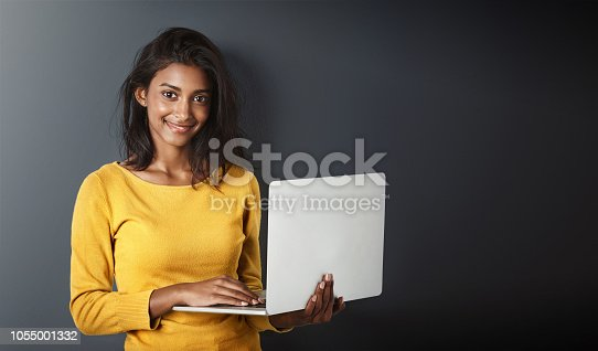 Studio portrait of an attractive young woman using a laptop against a gray background