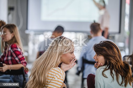 Female college students gossiping while being on a seminar at campus.