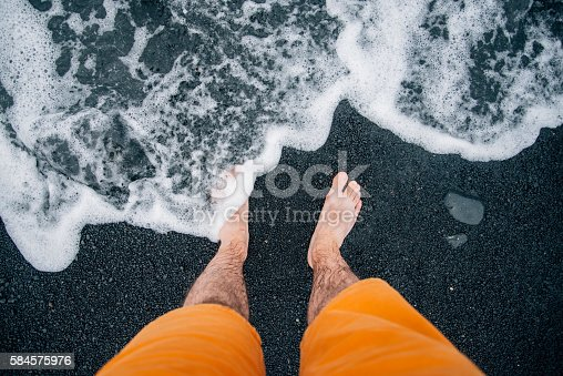A man's feet getting into the sea at a black sand beach in Lanzarote, Spain