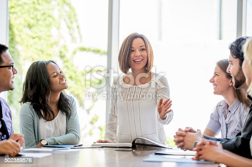 A businesswoman is presenting in a boardroom meeting at work to his coworkers.
