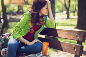 Sad woman with closed eyes sitting on the park bench and holding her head in hand