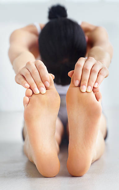 Having a good stretch Young woman touching her toes in a stretch touching toes stock pictures, royalty-free photos & images