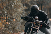 Young man driving custom made motorcycle in a leather jacket.
