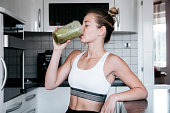 Beautiful young and fit woman having a blended fruit for breakfast