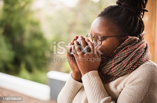 Shot of african woman on cold winter day wearing sweater and muffler drinking hot cup of coffee at a cafe