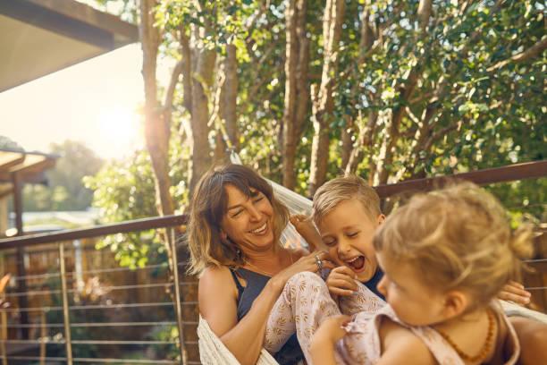having a laugh - mãe criança brincar relva efeito de refração de luz imagens e fotografias de stock