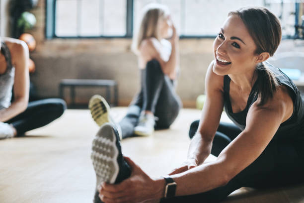 Having a laugh while limbering up Shot of mature women stretching with a young female instructor during a training class at the gym exercising stock pictures, royalty-free photos & images
