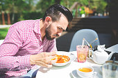 A photo of young man eating dinner in some cafe garden.