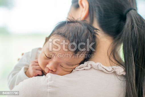 An Asian mother and newborn baby boy are indoors in a house. The baby is wearing a white sleeper. He is asleep in his mother's arms, and she is holding him over her shoulder.
