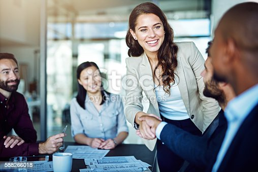 istock Cropped shot of two businesspeople shaking hands during a meeting in the boardroom 588266018