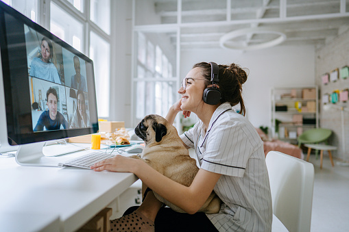 Photo of a smiling young woman having a video call, accompanied by her dog; the daily routine of a young woman working from home.
