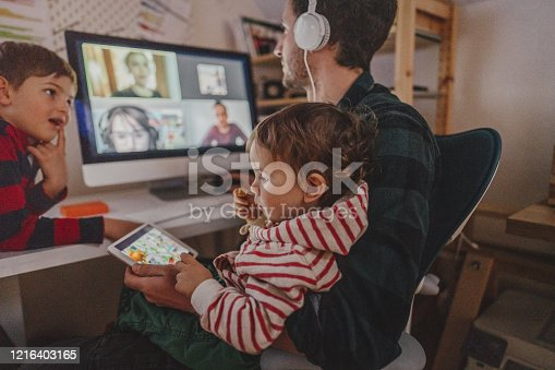 Photo of a man working from home, with his sons as a company, having a video conference call