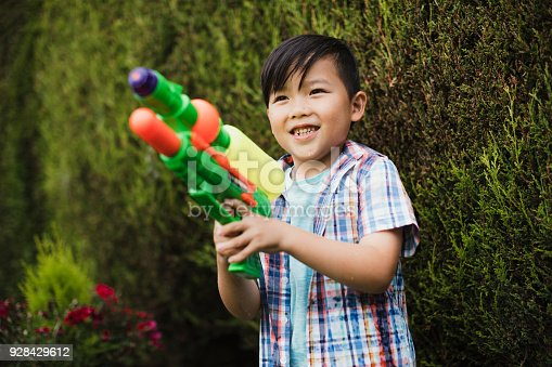 Little boy is having a water fight in the garden with his family. He is laughing with a water pistol in his hand.