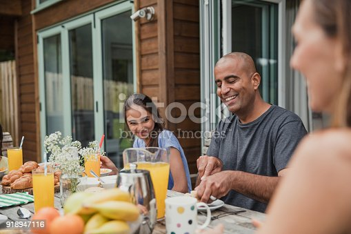 Family laughing and talking while father cuts some bread at breakfast.