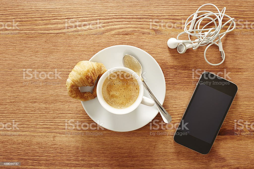 Having coffee and croissants with smartphone stock photo