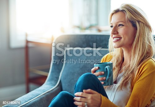 Shot of a young woman relaxing on her sofa with a cup of coffee