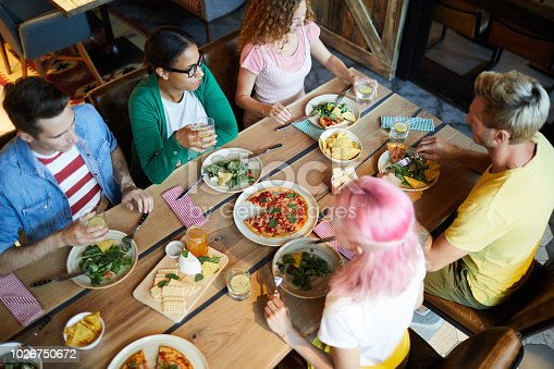 Overview of wooden served table with tasty meal and group of friends sitting around and having dinner