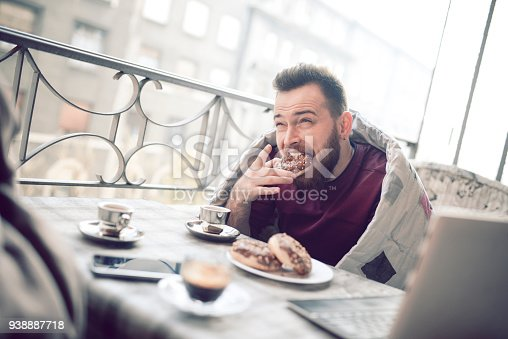 istock Having Donuts and Coffee in Front of Laptop on Balcony 938887718