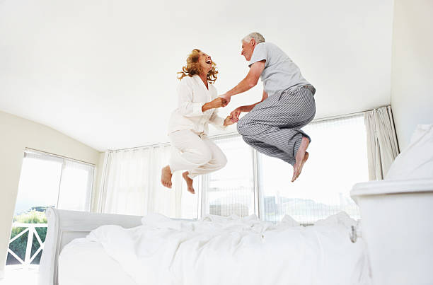 Having fun at any age! Excited senior couple jumping on their bed at home young at heart stock pictures, royalty-free photos & images