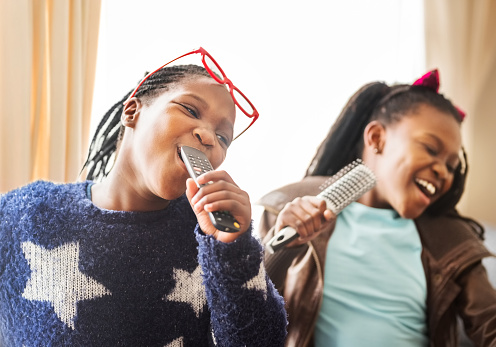 Shot of two girls singing together and having fun at home