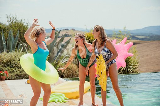 Group of mature female friends at a pool party by the water with inflatable rings.