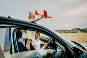 Photo of smiling family having fun on the road trip