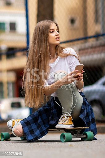 625928750 istock photo Having fun . Female Skateboarder is Using a Mobile Phone in the Street 1205072846