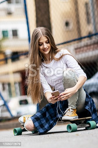 625928750 istock photo Having fun . Female Skateboarder is Using a Mobile Phone in the Street 1205072879